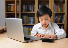 A boy in front of laptop computer and making calculations on calculator Royalty Free Stock Image