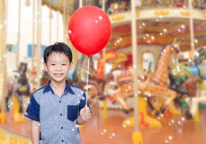 Boy in front of merry go round Stock Photo
