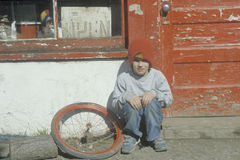 A boy in front of an old store with his bicycle tire Stock Photo