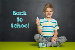 Boy in front of school board with text BACK TO SCHOOL Royalty Free Stock Image