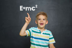 Boy in front of school board with text Emc2 Stock Photography