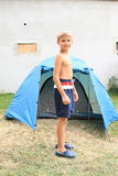 Boy in front of tent. Little boy - smiling boy standing in front of modern tent royalty free stock images