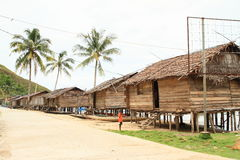 Boy in front of traditional fishers houses. Boy in front of traditional fishers house made from wood on pillars in Indonesian village - Papua Barat, Indonesia Stock Images