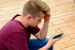 Boy in front of wooden ground using his phone Stock Images