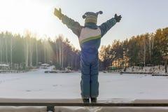 Boy at the frozen lake enjoys sunlight royalty free stock images