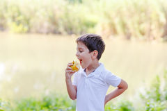 Boy with an fruit on the banks of the river. Boy biting an fruit on a river Royalty Free Stock Image