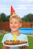 Boy with fruit pie, happy birthday party. Seven years stock photos