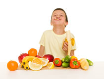 Boy with fruits and vegetables eat banana Stock Photography