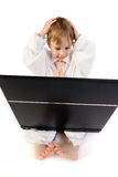 Boy frustrated with laptop. A picture of a young caucasian boy sitting with a laptop on his lap, hands on his head in shock/exasperation. He is dressed in an Royalty Free Stock Photos