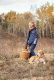 Boy with full basket of mushrooms with dog on the forest glade Stock Photo