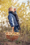 Boy with full basket of mushrooms in forest Royalty Free Stock Image