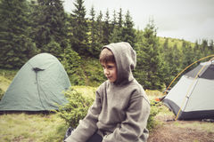 Boy with funny face, wearing hoodie, resting in camp Royalty Free Stock Photo