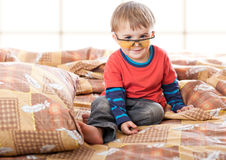 A boy in funny glasses on the bed Stock Photography
