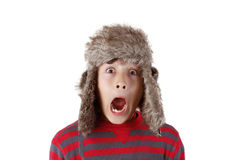 Boy in furry hat pulling funny face. S on white background Stock Image