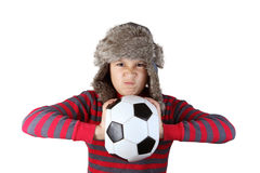 Boy in furry hat squeezing soccer ball Royalty Free Stock Image
