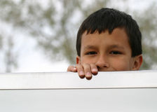 Boy Furtive Look. A young Latin American boy with furtive look peeks over the edge of the back of a truck bed Royalty Free Stock Photo