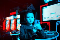 The boy in the game center shoots himself on video on the phone. Neon lighting. Boy blogger royalty free stock images