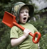 A boy in the garden. With red spade Royalty Free Stock Image