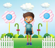 A boy in the garden with flower lollipops Royalty Free Stock Image