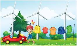 A boy in the garden with his car and hanging clothes Royalty Free Stock Photos