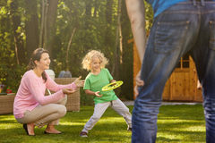 Boy in garden with parents. Small boy playing with parents in garden royalty free stock photos