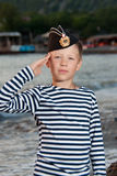 Boy in garrison cap and striped vest standing near the sea. On a background of mountains Stock Image