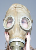 Boy with gas mask. Portrait of a boy putting on WW2 gas mask  - isolated on gray Royalty Free Stock Image