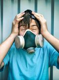 Boy in the Gas Mask. Toned Photo of a Boy in the Gas Mask on the Wall Background Royalty Free Stock Images