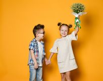 Image of young happy caucasian boy gives a flowers to his girlfriend isolated over yellow background. Boy gave a bouquet of flowers to the girl. Children hold royalty free stock images