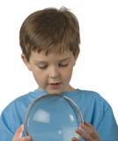 Boy Gazes into a Crystal Ball. Boy holds a crystal ball and gazes Stock Image