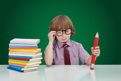 Boy genius with books and large pencil. Adjusting his glasses - on green background Royalty Free Stock Image