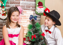 Boy gentleman and girl in ball dress by fireplace. Christmas Royalty Free Stock Photo