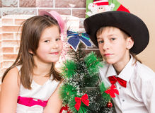 Boy gentleman and girl in ball dress by fireplace Stock Photo