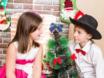 Boy gentleman and girl in ball dress by fireplace. Stock Images