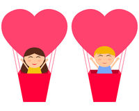 Boy and gerl sitting in hot air balloon in the shape of heart Royalty Free Stock Images