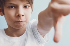 Boy gestures his finger down. Emotion concept stock image