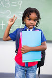 Boy gesturing while standing in classroom. Portrait of boy gesturing while standing against board in classroom Royalty Free Stock Image