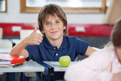 Boy Gesturing Thumbs Up In Classroom. Portrait of little boy gesturing thumbs up at desk in classroom Royalty Free Stock Photos