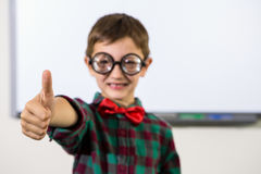 Boy gesturing thumbs up sign in classroom. Portrait of boy gesturing thumbs up sign in classroom Stock Images