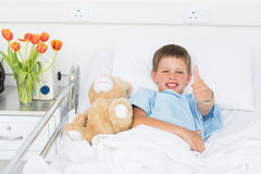 Boy gesturing thumbs up with teddy bear in hospital Stock Image