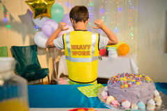 Boy gesturing to the text on protective workwear Stock Photography