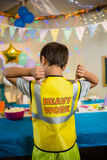 Boy gesturing to the text on protective workwear Stock Image