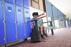 Boy gesturing while using virtual reality glasses on bench. By lockers in corridor at school Stock Images
