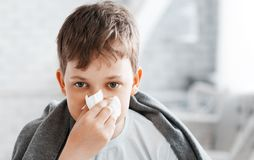 Boy get cold and blow her nose at home.  royalty free stock photography