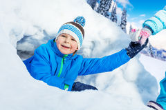 Boy get pulled out of snow tunnel in park Stock Photography