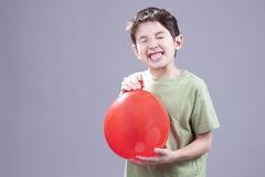 Boy gets air blast from balloon. Stock Photo