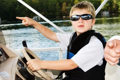 Boy gets direction from father. Young boy at the wheel of a boat learning to drive, he's asking directions from his father, reflected in his sunglasses. (He's royalty free stock photo