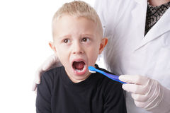 Boy gets help by the Dentist to brush his teeth Stock Image