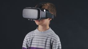 Boy getting experience in using VR-headset. Augmented reality device creating virtual space for smartphone applications. Shot of a boy getting experience in stock video footage