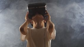 Boy getting experience in using VR-headset in a smoky dark room. Shot of a boy getting experience in using VR-headset. Augmented reality device creating virtual stock video